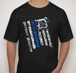 """Totally custom """"Distressed Flag"""" T-shirts exclusively from Detroit Holster featuring the """"Thin Blue Line"""" stripe. MADE IN USA! Also remember that Detroit Holster donates approximately 10% to charities that support military, law enforcement, the hungry and more – all thanks to your purchases. Thank you! Order yours HERE."""